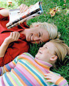 mama si fiica pe pajiste citind o revista