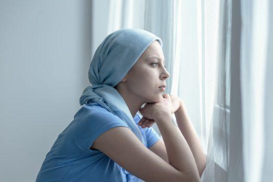 femeie care sufera de cancer se uita pe geam