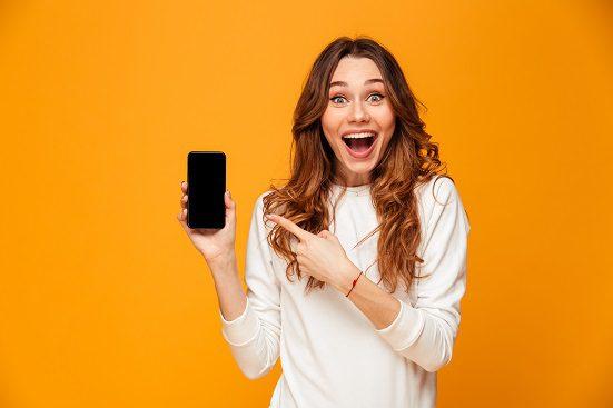 femeie fericita cu un telefon in mana