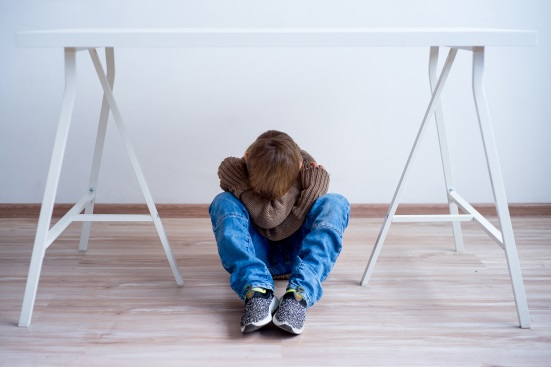 copil care sta cu genunchii apropiati de cap