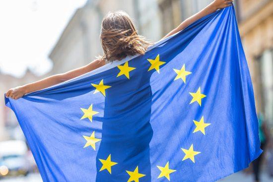 femeie cu spatele care tine steagul uniunii europene cu ambele maini